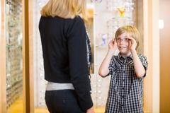 Boy Looking At Mother While Trying On Spectacles Royalty Free Stock Photography