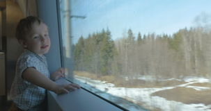 Boy looking at nature scene through the train. Little boy standing by the big window in moving train. He looking at passing winter or early spring landscape with stock footage