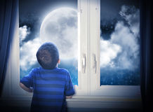 Boy Looking at Night Moon and Stars. A young boy is looking out of the window at a big moon in the dark night with stars and space for an astronomy or Royalty Free Stock Images