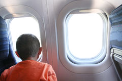 Boy Looking Out Jet Window. Young boy looking out the window of an airliner during a flight Royalty Free Stock Images
