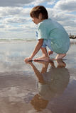 Boy looking out to sea. Little boy daydreaming and  looking out to sea Royalty Free Stock Image