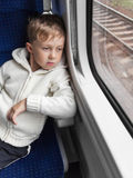 Boy looking out train window. Sad boy looking out the window of the departing train Stock Photography