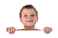 Boy looking out of whiteboard smiling isolated. Portrait of a preteen boy wearing yellow top, hidden behind a horizontal invisible empty banner, smiling a toothy Stock Images