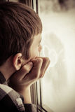 Boy looking out window with heart icon on glass Royalty Free Stock Photos