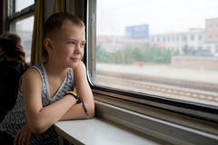 Boy looking out the window moving train Stock Photography