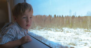 Boy Looking Out the Window of Moving Train. Little boy is looking out of the train window, he's very interested with the view stock video
