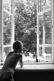 The boy is looking out the window. Boy without outer clothing looks at the open window Royalty Free Stock Photo