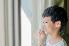 Boy looking out of window and smiles. Young Asian boy looking out of window in morning and smiles Royalty Free Stock Photography