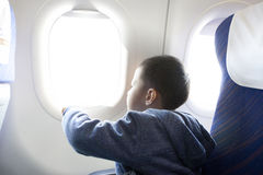 Boy looking outside of airplane window Stock Images