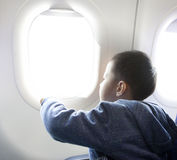 Boy looking outside of airplane window Royalty Free Stock Photo