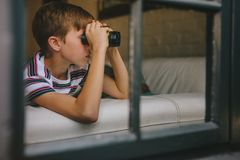 Boy looking outside window using binoculars stock photo