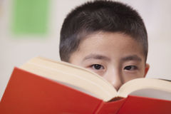 Boy Looking Over Book He's Reading Royalty Free Stock Photography