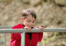 Boy looking over a railing at a bridge Royalty Free Stock Photography