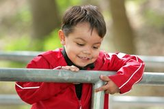 Boy looking over a railing at a bridge Stock Images