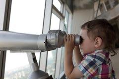 Boy looking through pay binoculars Royalty Free Stock Image