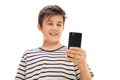 Boy looking at a phone and smiling Royalty Free Stock Image