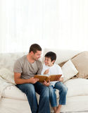 Boy looking at a photo album with his father. Adorable boy looking at a photo album with his father on the sofa at home royalty free stock photos