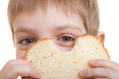 Boy looking through piece of bread Royalty Free Stock Photography