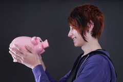 Boy looking pig money box Royalty Free Stock Photos