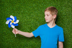 Boy looking at pinwheel over grass Royalty Free Stock Photography