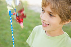 Boy looking at pinwheel in park Stock Photography