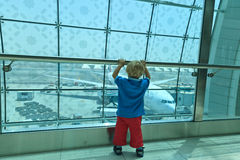 Boy looking at planes in the airport Stock Photos