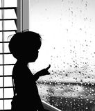 Boy looking at the rain drops on the window -  silhouette
