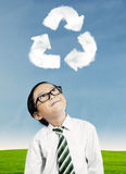 Boy looking at recycle symbol. Little boy looking at recycle symbol above his head Royalty Free Stock Photos