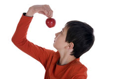 Boy looking at a red apple Stock Photo