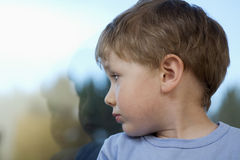 Boy Looking At Reflection Of Self On Glass. Cute little boy looking at reflection of self on glass stock photography