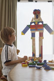 Boy Looking At Robot Made Of Blocks On Table Royalty Free Stock Photography