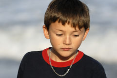Boy Looking Sad. A young boy, nine years old, looks down in a sad or contemplative mood. The setting sun gives the photo a warm tone Royalty Free Stock Photos