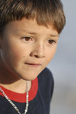 Boy Looking Sad Close-up. A young boy looking sad or in a serious mood. The setting sun gives the photo a warm tone Royalty Free Stock Images