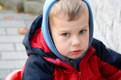 Boy looking sad outside in the cold Stock Images