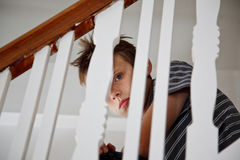 Boy looking scared through the handrail Stock Photos