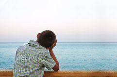 Boy looking at sea in the sunset Royalty Free Stock Photos