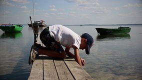 Boy looking for seashells on the pier in the river near the boat stock footage