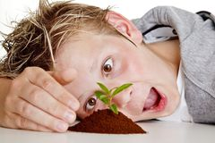 Boy looking at a small plant in soil. Teenage boy looking at a small plant growing in soil with a funny expression on his face Stock Photo