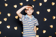 Boy looking for something on golden hearts background Stock Images
