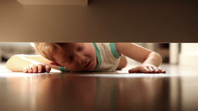 A boy is looking for something under the bed stock video footage