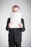 Boy looking at a stack of paper Stock Image