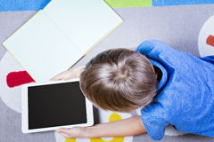 Boy looking at tablet pc, lying on the floor with books. At home. Top view Stock Image