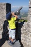 Boy looking through a telescop Stock Images