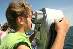 Boy looking through telescope. Boy looking through silver coin operated pay binoculars deco style Stock Photo