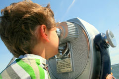 Boy looking through telescope. Boy looking through silver coin operated pay binoculars deco style Stock Images