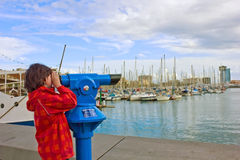 Boy looking in telescope. In port of Barcelona, Spain Stock Photo