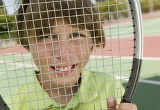 Boy Looking Through Tennis Racket portrait close up Royalty Free Stock Photo