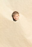 Boy looking thru hole Royalty Free Stock Photo