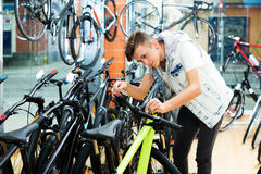Boy looking for and trying new racing bicycle Royalty Free Stock Images