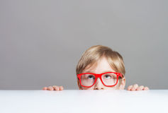 Boy looking up from behind the table Royalty Free Stock Photos